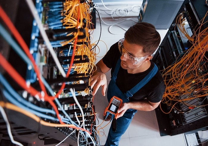 The Best Business Internet Providers, a young man measures internet equipment in the service center.