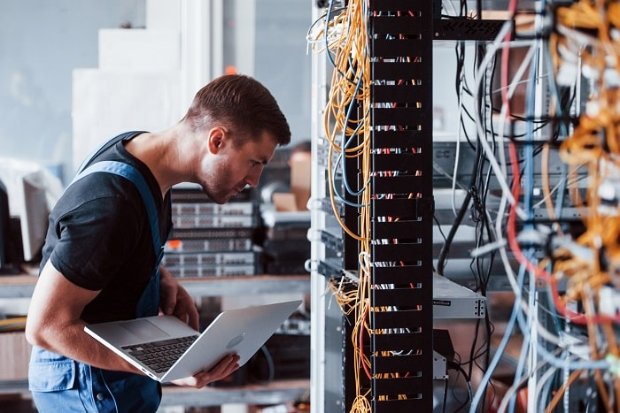 in this picture a male technician is working in a telecommunication center on a laptop.